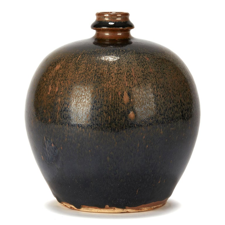 A stylish Chinese art pottery vase of rounded bulbous shape with a bottle shaped neck and opening and decorated in black haresfur style glaze on a brown ground. The vase has an unglazed foot and base and is not marked.  OR19188.