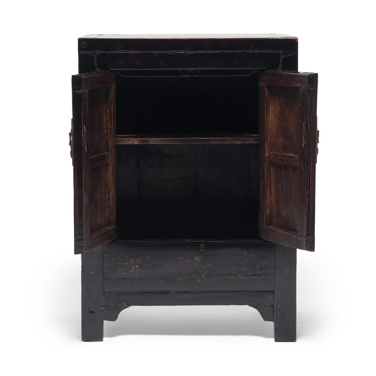 Perfecting line and proportion, the simple design of this low square corner cabinet celebrates the restraint of classic Chinese furniture forms. Dated to the mid-19th century, the chest is crafted of elmwood and cloaked in layer upon layer of black