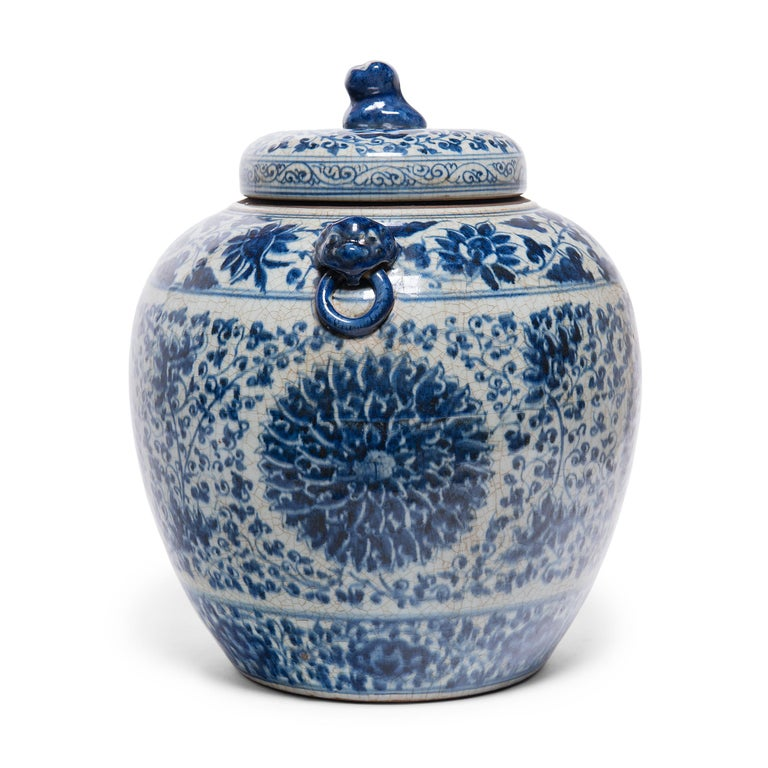 This gorgeous ginger jar continues a centuries-old tradition of Chinese blue-and-white porcelain ware. Painted with expressive brushwork, the jar is festooned with trailing vines and flower blossoms, densely patterned around large chrysanthemum