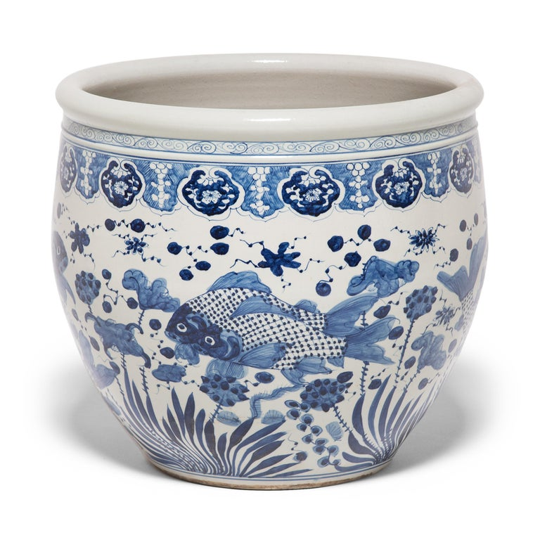 This grand, blue-and-white porcelain bowl is hand-painted with flora and fauna of the sea, offering blessings of wealth, abundance, and the contented harmony of a fish in water. Chinese blue-and-white ceramics have inspired ceramists worldwide since
