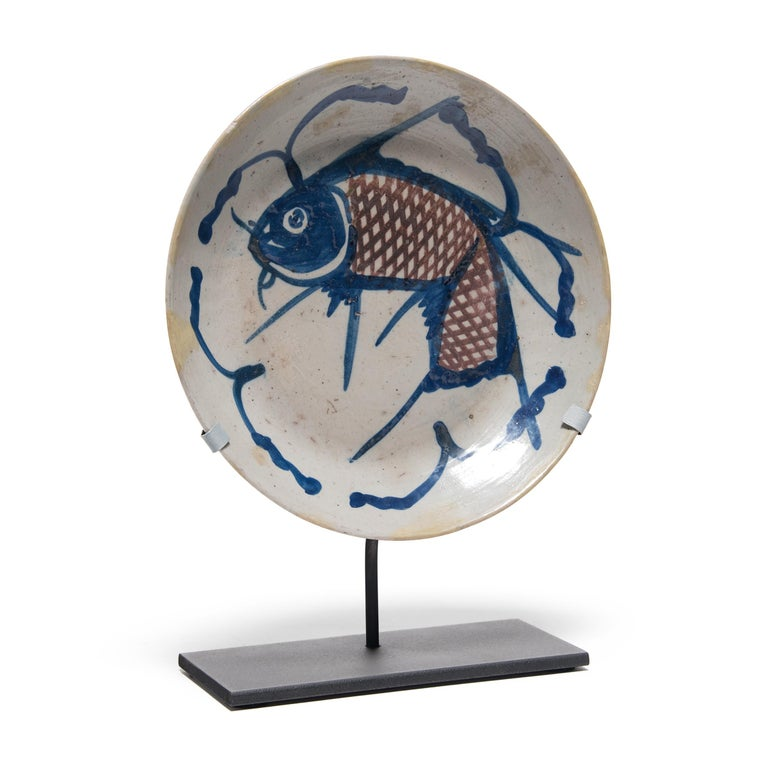 A traditional motif in Chinese art, the fish on this hand painted 19th century provincial plate represents a blessing for wealth. Chinese symbols take on added meaning and nuance when seen in combination. In this plate, the decorative blue lines