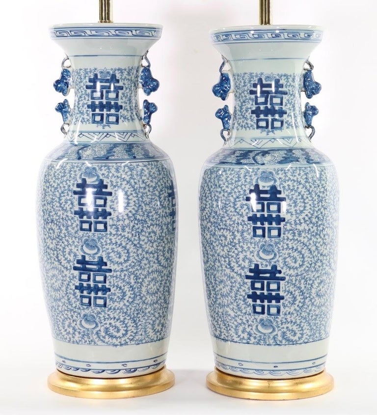 Pair of large Chinese blue and white porcelain vases mounted as table lamps, with double happiness symbols, dating from the early 20th century and mounted on gilt wooden bases.