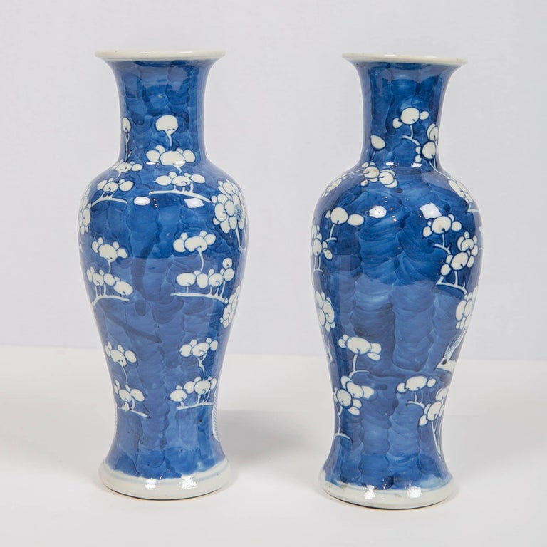 We are pleased to offer this pair of antique Chinese blue and white vases made in the late Qing period of the 19th century, circa 1880. They are decorated with white plum blossoms. The white blossoms are set on a subtly crackling blue ground. The