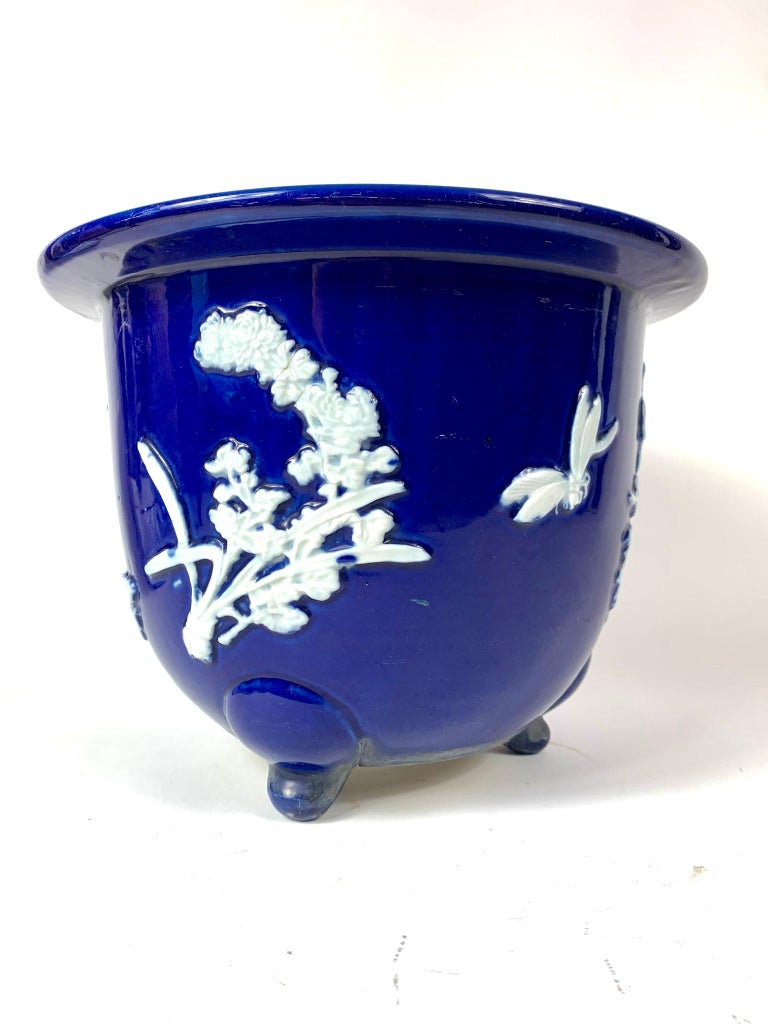 Chinese Pâte-sur-pâte jardinière in cobalt with raised white area decorated with flowers, butterfly and dragonflies. The bottom has three feet and a hole for water to drain through.