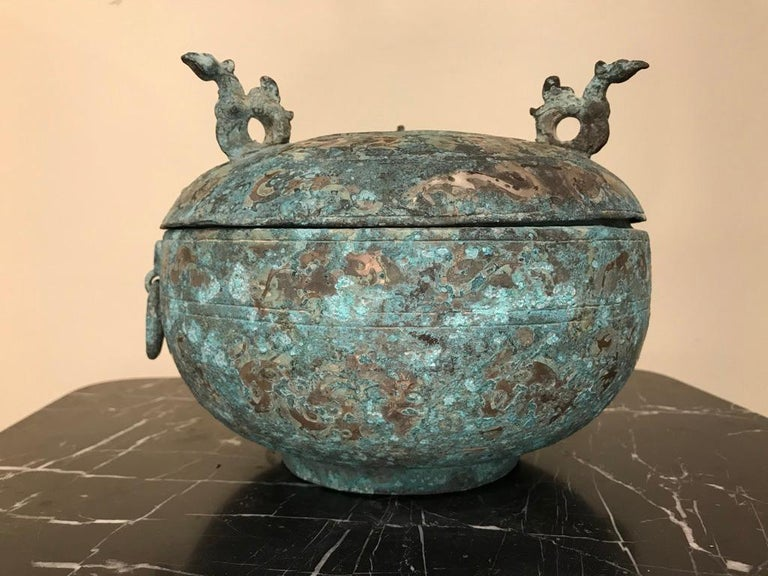 A Chinese silver inlaid bronze lidded ritual vessel modeled after a late Shang dynasty, 1600-1046 BC original. Of Classic form, with bird form handles on the top and ring handles held by Taotie masks on the bowl. The overall surface covered with