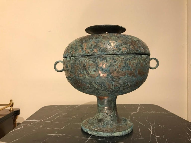 A Chinese silver inlaid bronze lidded ritual vessel modeled after a late Shang dynasty, 1600-1046 BC original. Of Classic form, with ring handles, the surface covered with inlaid Archaistic designs. The silver mixed with verdigris patina give this