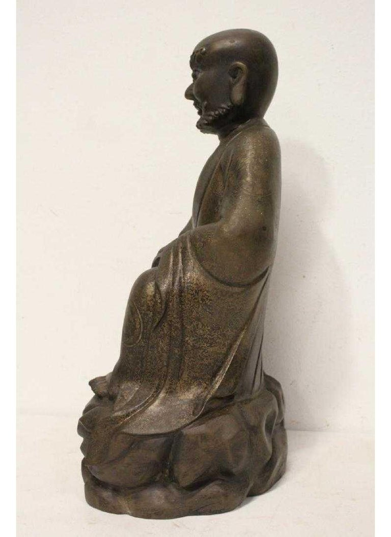 Imposing and large Chinese bronze seated Lohan with decorated dress, mid-20th century. Finely detailed Lohan in traditional Chinese garments in meditative seating, all resting on rock platform. Signed.   Bring your gaze to the meticulous attention