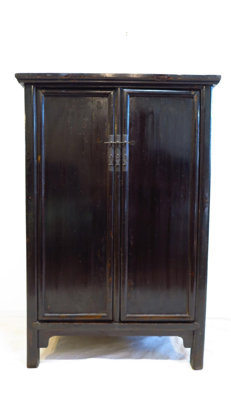 19th century black lacquer Chinese cabinet. Referred to as a Chinese round corner cabinet, also a book cabinet. Wood hinged doors with a removable center stile. Two drawers inside with shelf space of 21H top and 19H bottom. Shandong, 1830-1850.