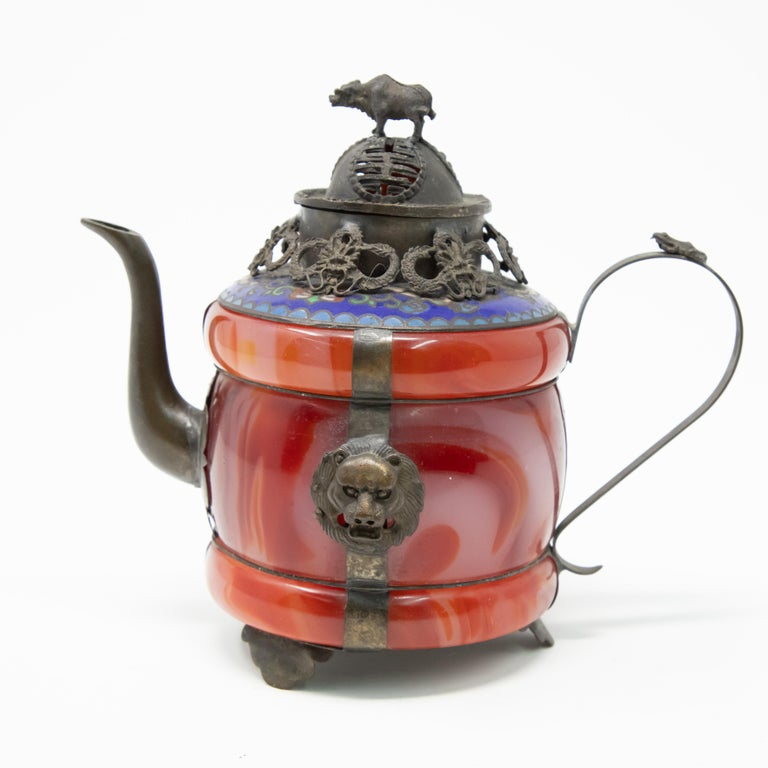 Offering this unmatchable Chinese teapot made of carnelian stone with enameled bronze and filigree. Starting on a footed bronze base the carnelian stone is attached with bronze bands to the base. Off of one of the bands the handle is attached with a