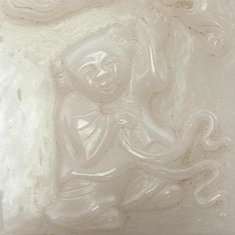 This jade pendant is carefully hand carved with a scene of a young boy playing outdoors. Above him are swirling clouds and a bat, a symbol of happiness and good fortune. Sometimes referred to as ho ho boys, children were a popular motif in Chinese