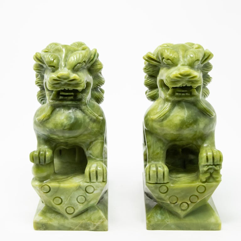 Offering this pair of stunning carved jade guardian lions. On rectangular plinths with geometric patterns and circles they rise up. One is guarding a ball under one foot and the other a baby lion. The carving of these are simple and the manes have