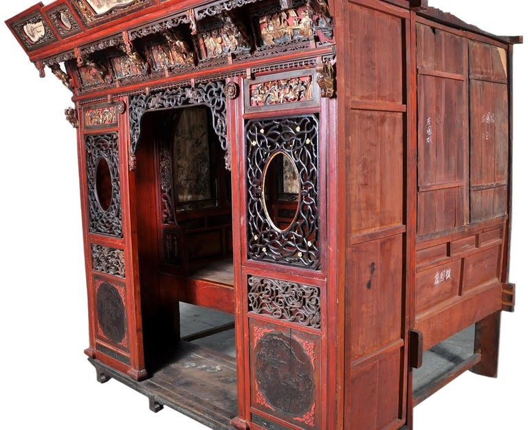 Chinese carved wedding bed, Qing Dynasty, circa 1880. The bed is finely carved, poly-chromed, and lacquered, most likely Cantonese. The cornice having reticulated and hand painted panels, below are deeply carved panels with scenes representing