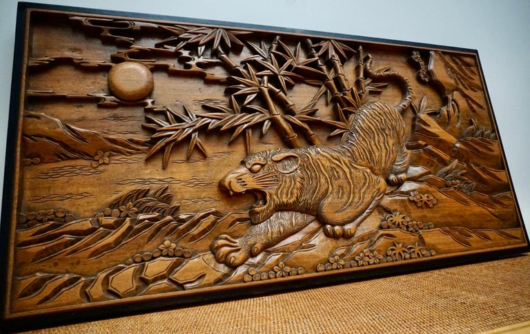 A large 19th century Chinese carved wall plaque in wood features a hunting tiger on rocks with bamboo trees and the sun in the background.
