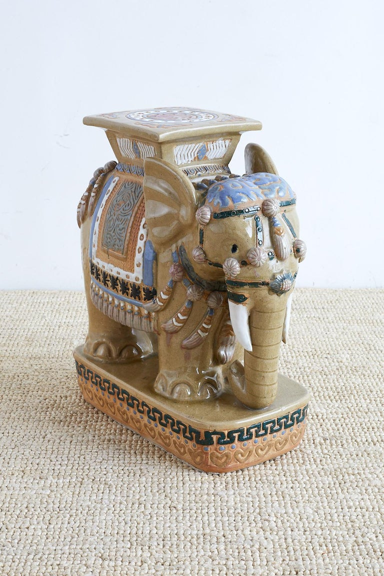 Colorful Chinese ceramic elephant garden seat or drinks table. Features caparisoned body with vibrant blue accent colors. Standing on an oval plinth with decorative designs.  Offered by Erin Lane Estate, Oakland, CA.