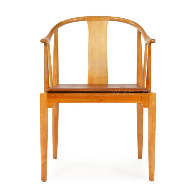 A cherry Chinese chair with a natural leather seat cushion.