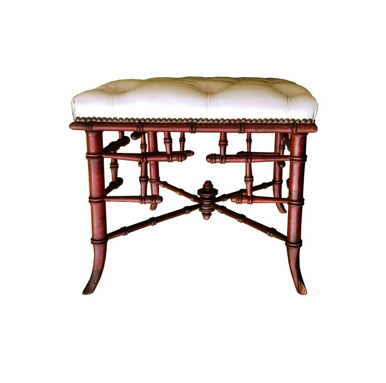 English mahogany wood ottoman late 19th century or early 20th century  This stool is in excellent condition.  Upholstered with broken white synthetic leather capitone.
