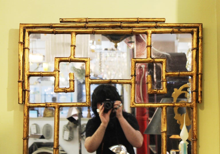 Chinese Chippendale gilt metal faux bamboo wall mirror, made during the 1970's. In great vintage condition with age-appropriate wear and use.