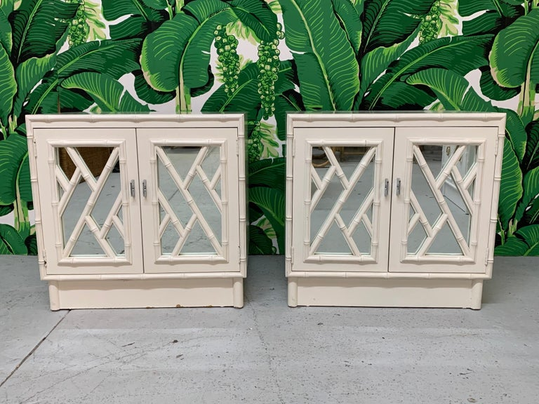 Pair of Hollywood Regency style nightstands feature chinoiserie pattern detailing over mirrored doors. Good condition with minor imperfections consistent with age.
