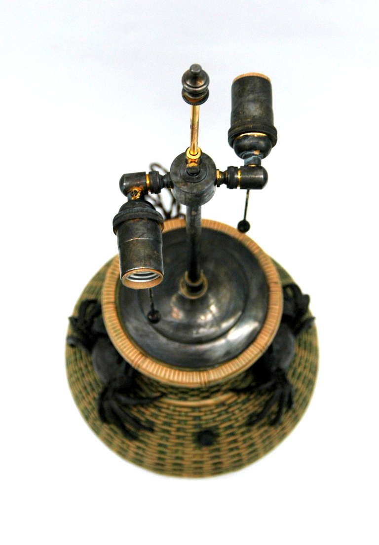 An original Chinese clay container made into a table lamp. The vase has a basket weave motif throughout and has two big black crabs and a small black conch as ornaments. There is an unidentified marking on the underside of the lamp.   All lighting