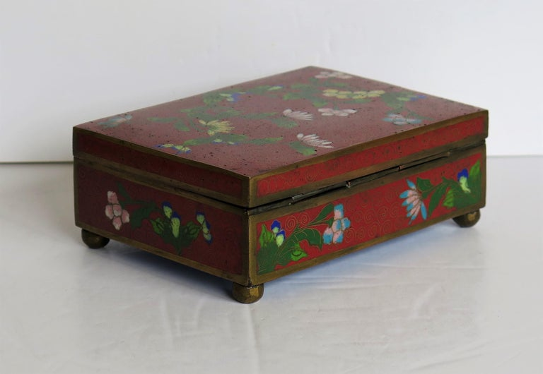 This is a good Chinese cloisonné box with a hinged lid and floral decoration which we date to the late Qing Dynasty, circa 1900.  The rectangular box is raised on four small bun feet and has a hinged lid.  The decoration is on all four sides of