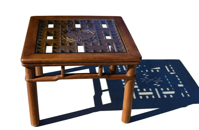 A beautiful natural finish square table made of solid elmwood. The tabletop inset with an antique screen has rounded corners and carved surrounds creating a double illusion. The tabletop continues on to a set of tiered stretchers which are fitted