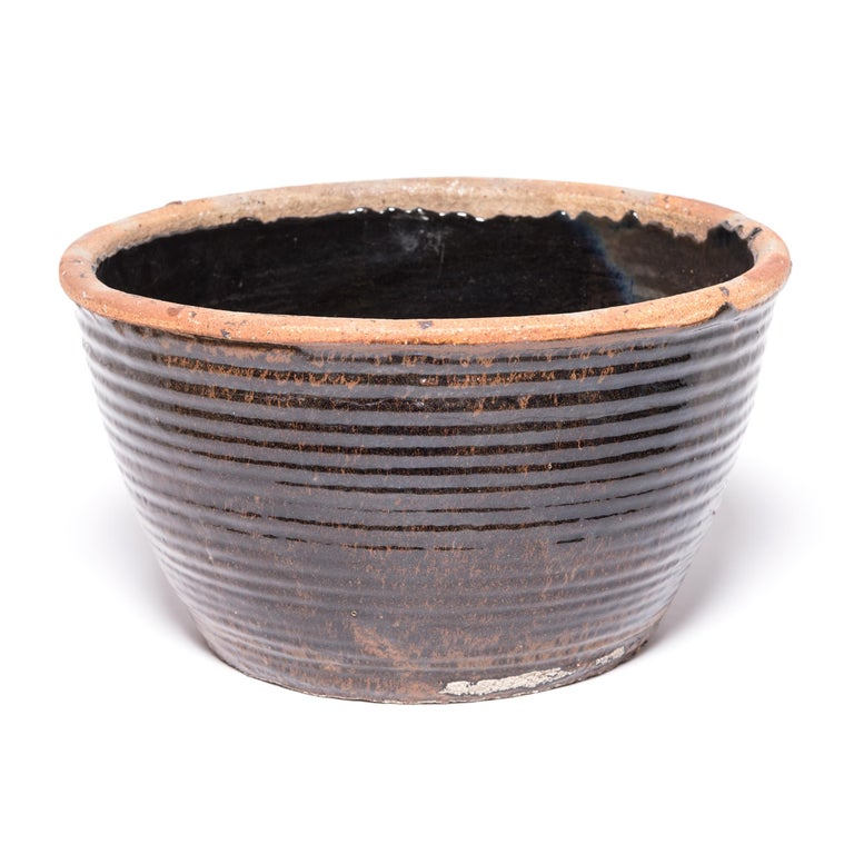 Originally used for pickling foods, this mid-20th century ceramic jar is coated inside and out with a dark glaze. Subtle ridges suggest that the bowl was fashioned by coiling flattened ropes of clay into the desired shape. Featuring an unglazed rim
