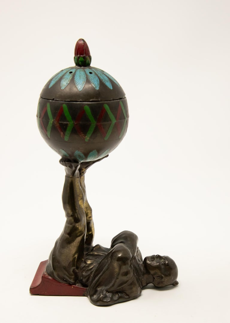 Offering this unusual cold-painted bronze Chinese censer. The base is a man lying on his back with a wedge under his legs. The legs are together and upward holding a sphere. The sphere is cold-painted with geometric designs. The sphere is where the