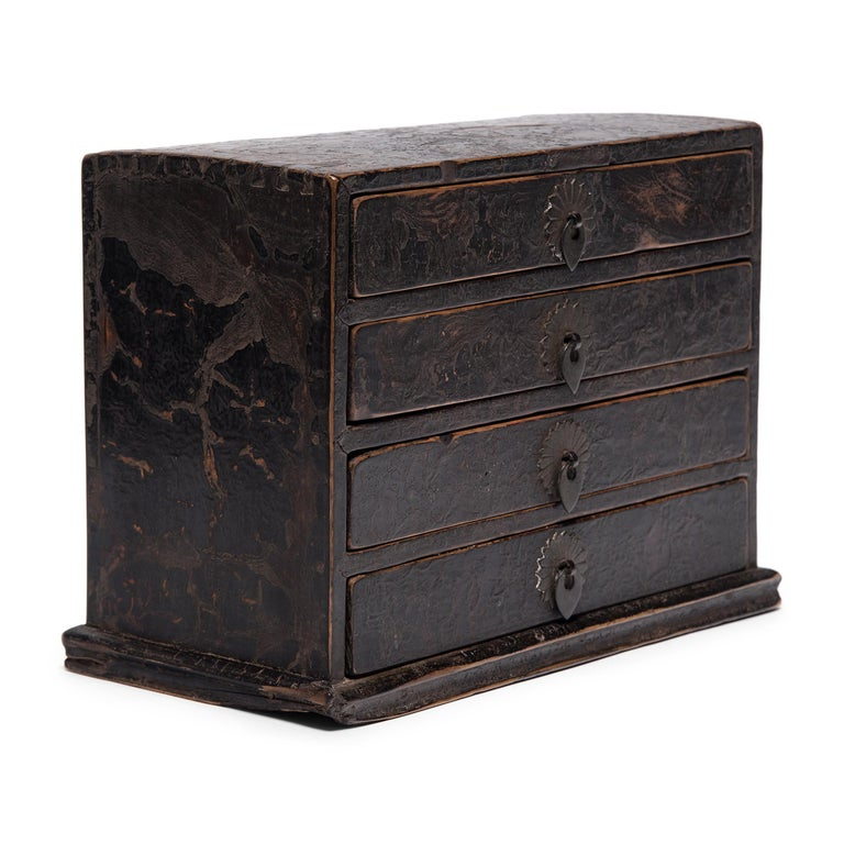 This petite 19th century chest of drawers is a fantastic example of the multifunctional boxes used tabletop in lieu of a larger cabinets. Such boxes were used to store cosmetics, jewelry, documents, and other accessories. This box has four shallow