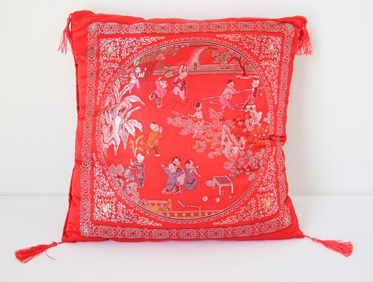 Asian decorative throw pillow with fringes and red tassels. Luxury silk in red with scene of kids playing outdoor in traditional Chinese costumes.