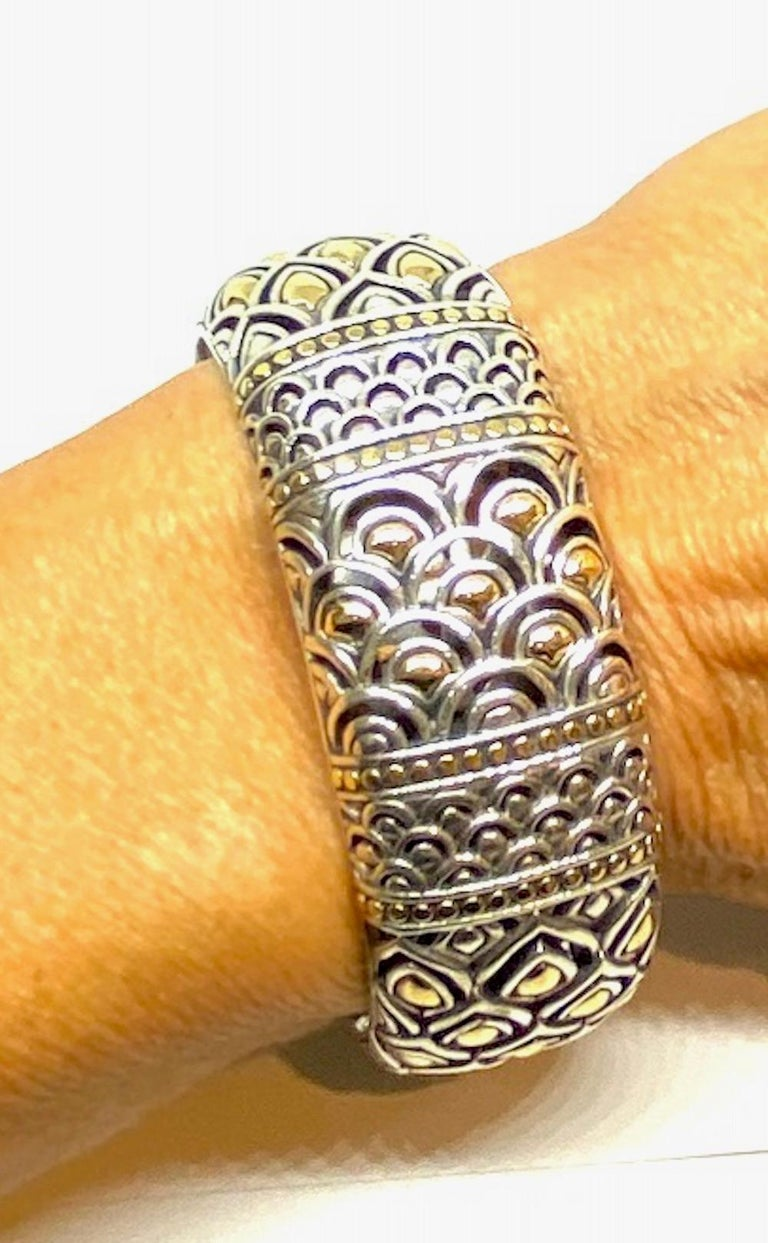 Wide 1 Inch Wide, Sterling and Gold Bangle Bracelet  Double thick and heavy with inside, two sided Dragons and Chinese motif Top of cuff displays sterling and 18 karat yellow inset within cut-outs of waves and scrolls. Bracelet hallmarks are a