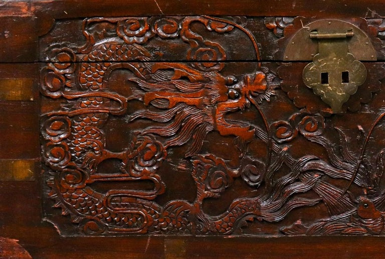 Chinese carved wood trunk chest, the hinged lid and front with elaborate dragon carving, metal lock and handles to sides, marked to interior: