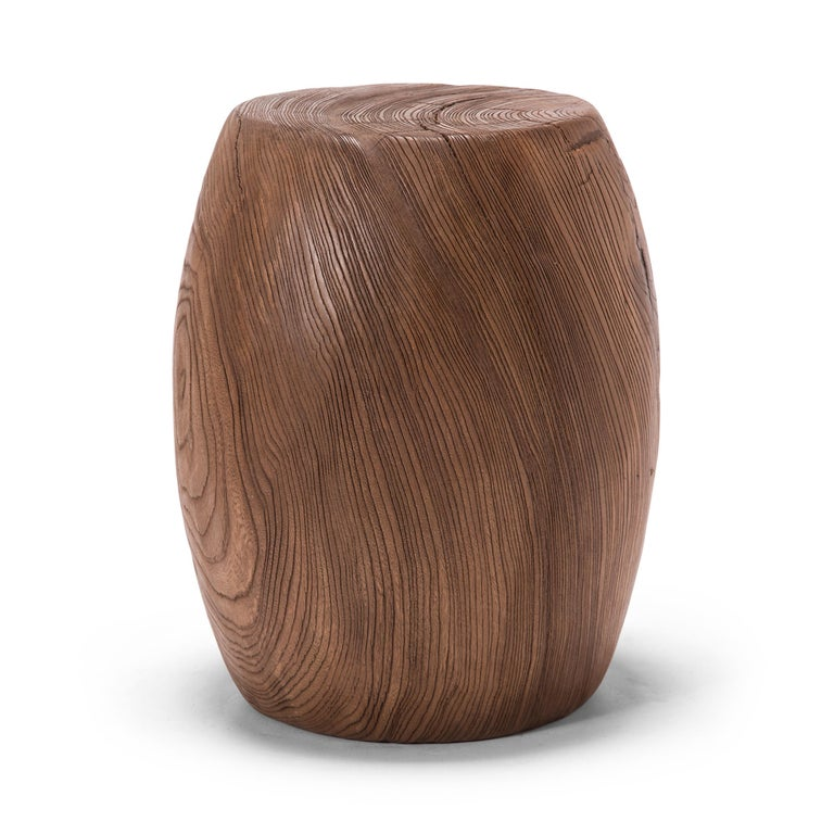 Honoring the traditional drum-form shape common of garden seats, this low table was carved from a single piece of northern elmwood to reveal mesmerizing grain patterns and growth rings. The expressive grain ebbs and flows like an calm river current