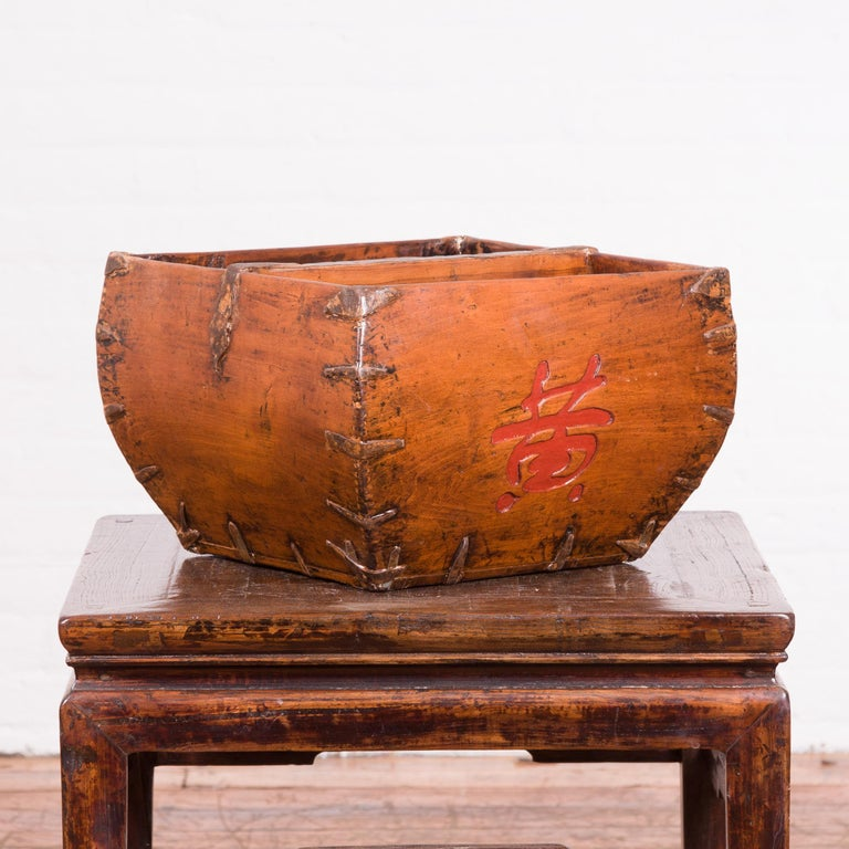 A Chinese antique grain basket from the early 20th century, with red calligraphy. Created in China during the early years of the 20th century, this grain basket features a square tapering body accented with braces in the corners and red calligraphy