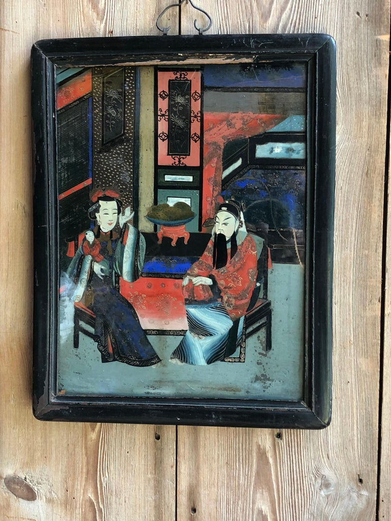 An early 19th century Chinese reverse painting on glass of a couple with a small child in a room, in original teak frame.