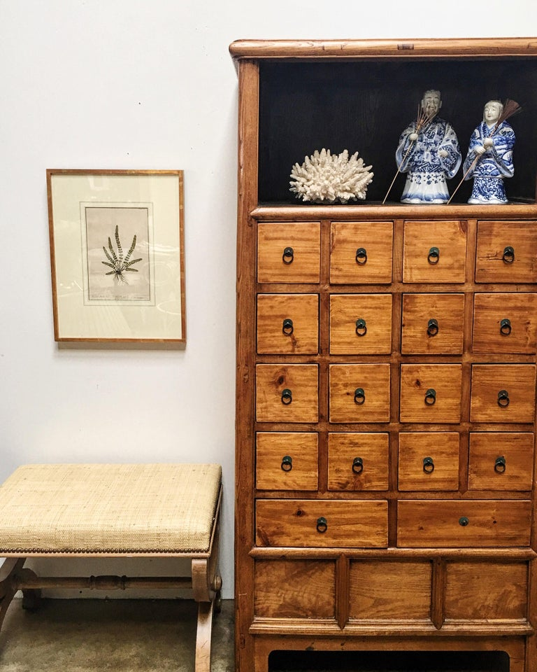Impressive Chinese tapered apothecary herbal cabinet constructed of elm and made with mortise and tenon joinery. Featuring 18 drawers, each having a ring pull mounted on an antique Chinese coin ring. The top has an open storage shelf and the bottom