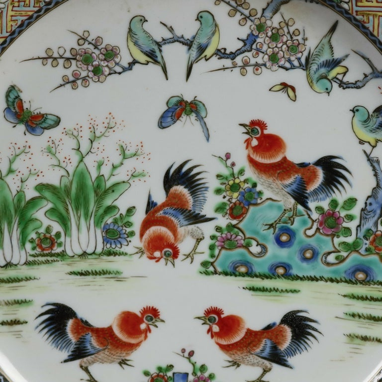A pair of Chinese hand enameled pictorial plates offer central garden scene with roosters, birds and butterflies, rim having basket weave border with foliate reserves, 19th century  ***DELIVERY NOTICE – Due to COVID-19 we are employing NO-CONTACT
