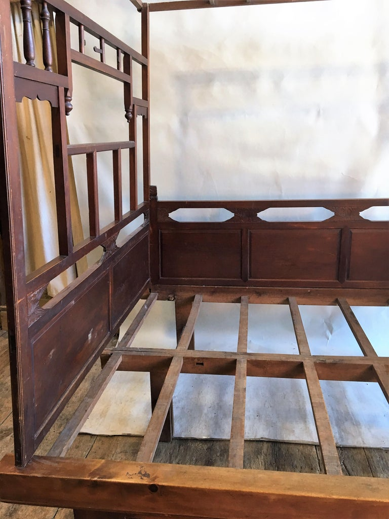 A Chinese wedding bed in carved wood, with lattice canopy supported by side walls with turned wood spindles and carved panels, circa 1890. The bed completely disassembles in minutes and can be easily transported. The base is in 2 halves.