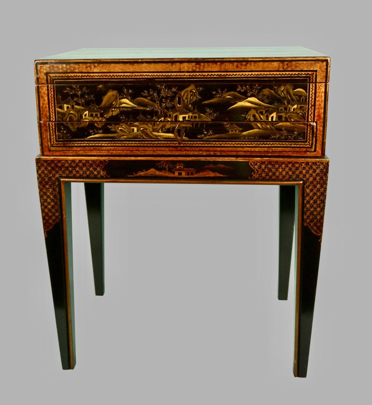 A pretty Chinese export black lacquer work box with a central drawer and side handles, the fitted interior with a retractable slide and pen tray, now mounted on a later custom made Chinoiserie stand. Box circa 1870-1890.