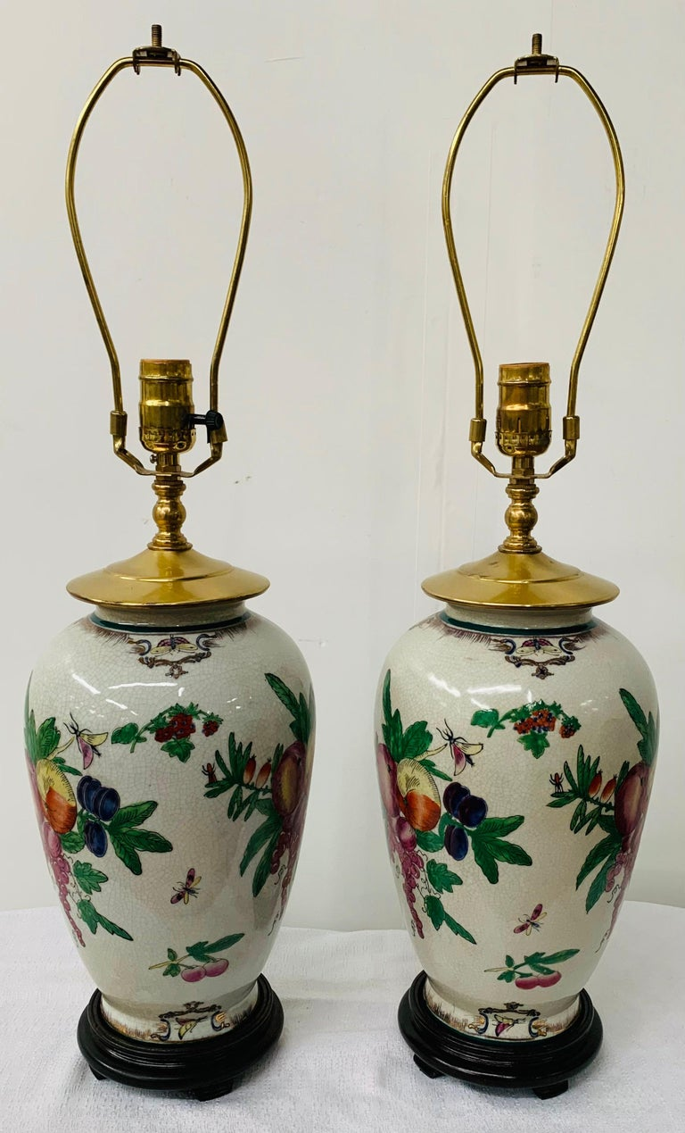 A beautiful pair of Chinese Export table lamps featuring an exquisite flora design. Both lamps sit on wooden carved base and come with white shades.   This pair of lamps will add style to your bedroom, living room, study/office space or entry