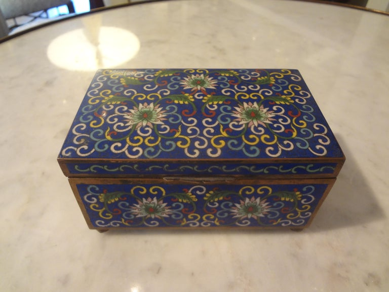 Lovely Chinese export cloisonné box made of brass and enameled with a beautiful floral pattern resting on ball feet. This chinoiserie box is marked China and dates from 1900-1920. This good sized decorative box was most likely a cigarette box or