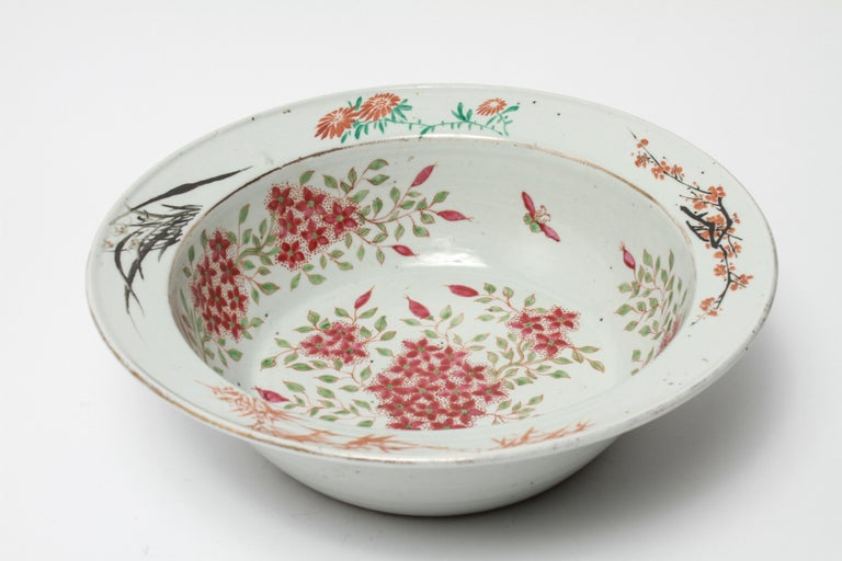 Chinese export Famille rose porcelain large bowl or basin. The piece has a polychrome floral motif and a gilt trim. In great vintage condition with age-appropriate wear and wear to the gilt trim.