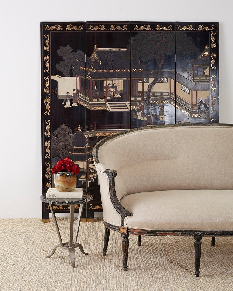 Elegant Chinese export four panel lacquered Coromandel screen. Featuring a courtyard scene amid pagoda structures and trees. Figures of elites in beautiful robes decorate the scene. The front panels are bordered with a gilt dragon motif and the