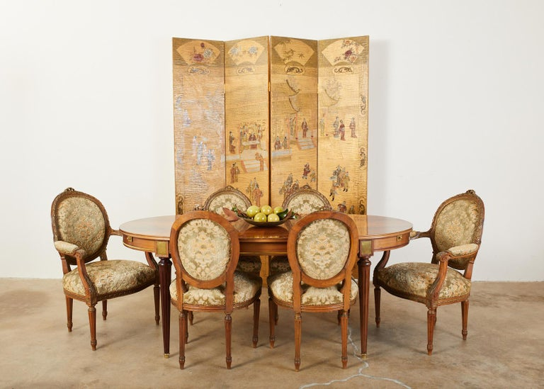 Qing style Chinese export four panel lacquered folding coromandel screen featuring a dramatic gilt background. The front of the screen is decorated with a pagoda court scene with figures engaged in leisurely activities. The scene is bordered with a