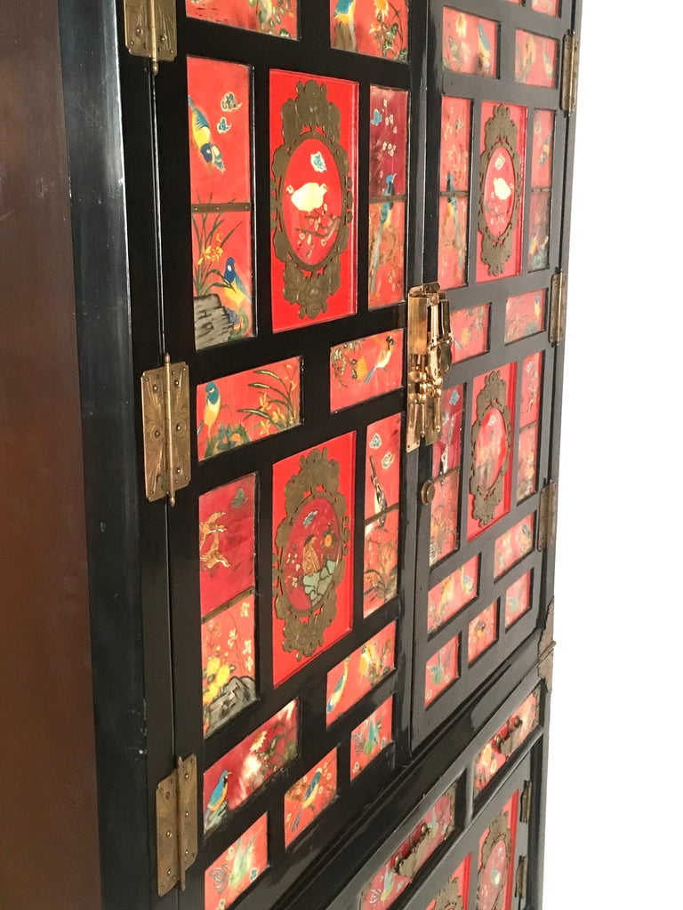 A striking Chinese export black lacquered cabinet of rectangular form, the front decorated overall with inset panels of hand-painted colorful birds on a red field, with brass mounts, shaped and engraved in butterfly and moth forms, comprising two