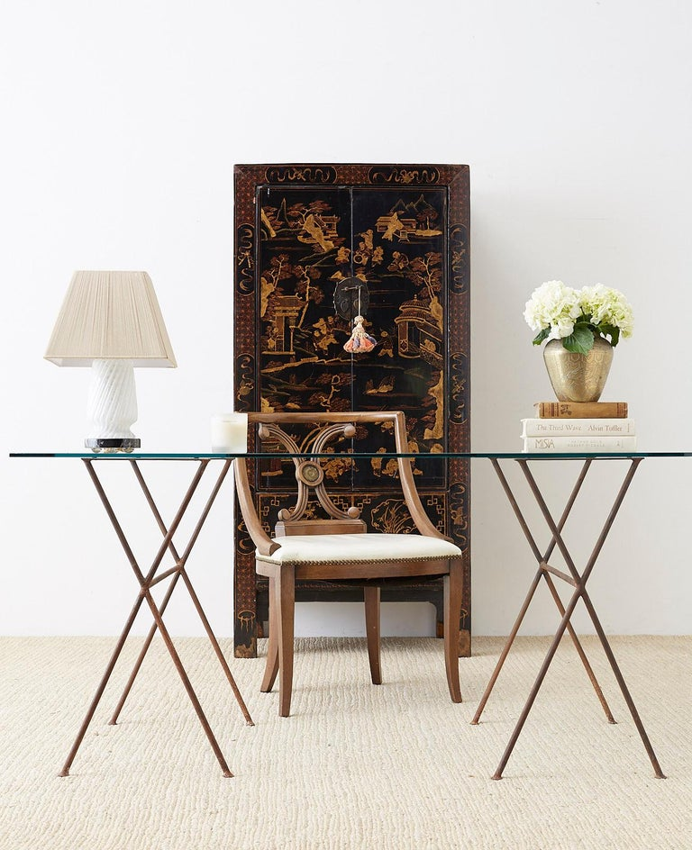 Marvelous Chinese export lacquered wedding cabinet or chest. Features a highly decorated parcel gilt front with young boys playing amid trees and pagodas. Fronted by two large doors that open to a one shelf storage area with two drawers. The doors
