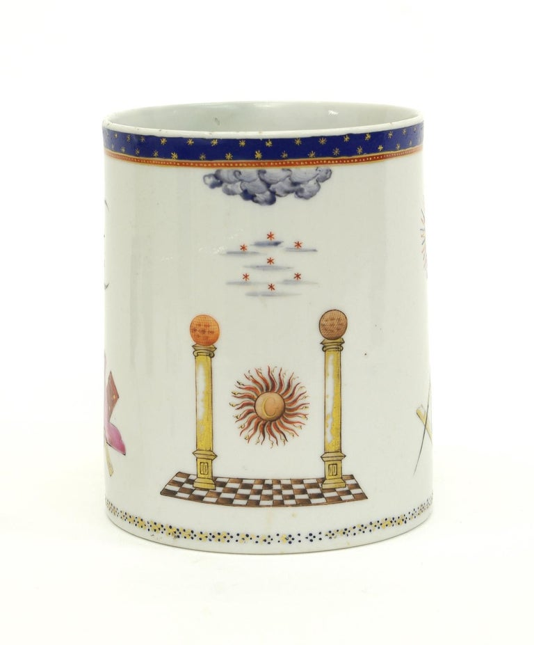 Chinese export porcelain Masonic cider mug, the cylindrical body with a double strap handle, decorated overall with Masonic emblems beneath a blue enamel band with gilt stars. Bears an S. Marchant & Son label to the bottom.  Restored chip to the