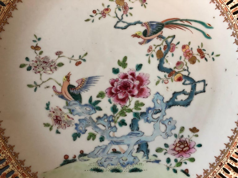 The Qianlong dish with famille rose enamels and gold paint, the central decoration composed of finely painted peonies and phoenixes resting on a tree, with openwork rim.