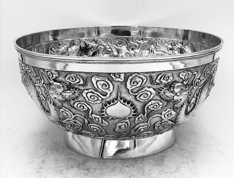 A Chinese export silver bowl, profusely decorated with dragons among clouds on a matte background. The bowl has a vacant cartouche, and is from Shanghai (上海) circa 1890. Marked by the maker '雄甡' (XiongShen), and the retailer 'Luen Wo' (联和).