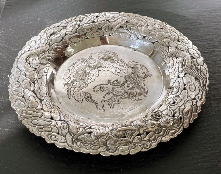 An elaborately decorated silver serving dish or butler's tray, likely dated to the turn of the 20th century, made in China for the export market. The round tray has a solid center in contrast with a pierced outer band of repoussé design that depicts