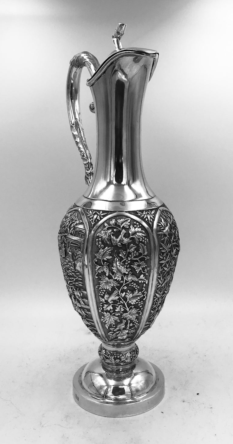A Chinese silver jug of tall, elegant form, decorated on six panels with birds among flowers, and figural court scenes. It has the mark of Hui as the silversmith. Along with the mark of the retailer Sun Shing. It dates from circa 1870. The jug